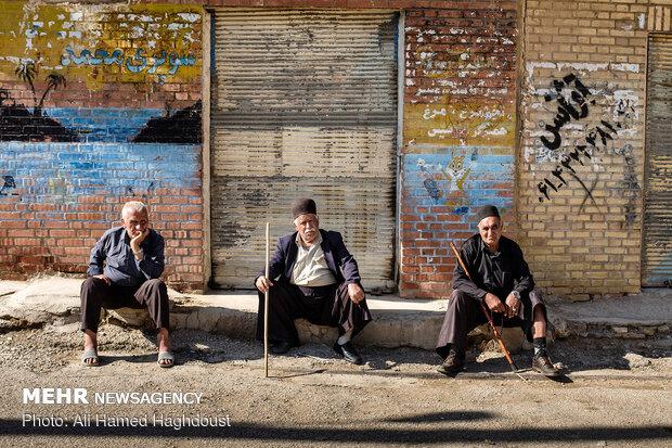 مردان بختیاری از راست، بارانه رضایی 70 ساله، فتح الله کیانی 65 ساله و علی عباس کریمی برای استراحت و گذراندن وقت در مقابل مغازه بسته ای در محله کلگه نشسته اند.