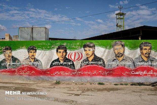 تصاویری از شهدای شهر مسجد سلیمان که در جنگ تحمیلی شهید شده اند، برروی پرچم جمهوری اسلامی ایران بر دیواری در محله کلگه کشیده شده است.