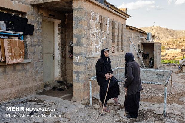 فاطمه سلطانی 88 ساله در حالیکه مقابل خانه قدیمی شرکت نفت در روستا نفت سفید نشسته، با همسایه خود کنیز آستریکی 94 ساله در حال صحبت است.