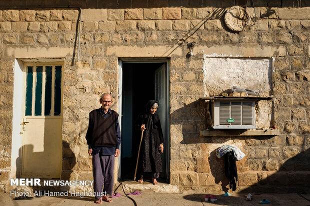شهاب علی سلطانی 86 ساله و همسرش فاطمه سلطانی 88 ساله در حیاط یکی از خانه های قدیمی شرکت نفت در روستای نفت سفید ایستاده اند. شهاب علی سلطانی از کارکنان بازنشسته شرکت نفت است که بر روی دکل حفاری کار می کرد.