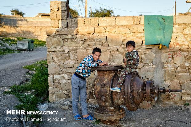 محمد یوسفی 13 ساله، (چپ) و پسر عمویش ابوالفضل یوسفی 4 ساله  بر روی شیر چاه پلمپ شده نفت که در کنار دیوار خانه ای در محله نفتون در شهر مسجد سلیمان قرار دارد نشسته است.