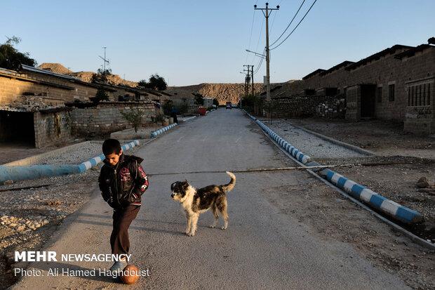 محمد چالنگ 10 ساله کنار سگ خود در یکی از محلات روستای نفت سفید در حال توپ بازی است.
