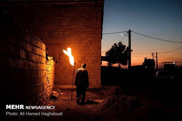 البرز سلطانی 65 ساله کنار مشعل برافروخته خانه خود درروستای نفت سفید می گذرد. اهالی این روستا برای روشنایی شب از مشعل های گاز استفاده می کنند.