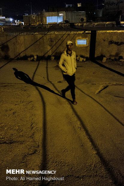 جوانی در شب از یکی از کوچه های محله کلگه عبور می کند. کلگه یکی از محلات حاشیه نشین و فقیر نشین در شهر مسجد سلیمان است.