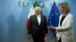 European Union High Representative Federica Mogherini (R), greets Iranian Foreign Minister Mohammad Javad Zarif prior to a meeting in Brussels on Monday, March 16, 2015. (Photo by AP)