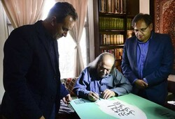 Actor Mohammad-Ali Keshavarz (C) signs a poster for the National Dramatic Arts Day at his home in Tehran