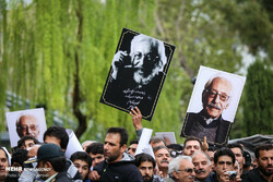 Fans hold pictures of legendary actor Jamshid Mashayekhi in his funeral in the courtyard of Tehran's Vahdat Hall on April 6, 2019. (Mehr/Maryam Kamyab)