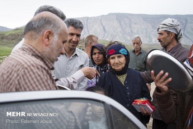 بی بی سکینه برای گرفتن وسایل آشپزی از خیرین، درکناردیگر روستاییان در صف ایستاده است