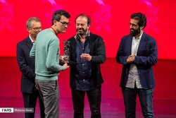 "Russian cinematographer Ayrat Yamilov (2nd L) receives the award for best film on behalf of ""A Russian Youth"" director Alexander Zolotukhin during the 37th Fajr International Film Festival"