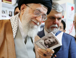 "Leader of the Islamic Revolution Ayatollah Seyyed Ali Khamenei glances at ""A Selection of Ahmad Shamlu's Poems"" at the pavilion of Morvarid Publications at the 32nd Tehran International Book Fair on A"