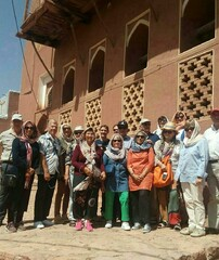 Foreign travelers pose for a photo during their visit to Abyaneh, an ancient village in Isfahan province.