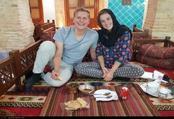 An international couple pose for a photo while staying in a traditional eco-lodge in Iran.