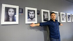 "Germany-based Iranian photographer Arasch Zandieh poses with some of his works on display in the exhibition ""Hope"" at the University of Gottingen, Germany. (Zandieh.de)"