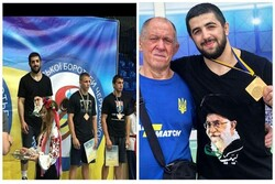 Ukrainian wrestler stands on champ's podium with image of Islamic Revolution Leader on his T-shirt