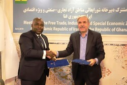 Secretary of Supreme Council of Iran's Free Trade, Industrial and Special Economic Zones Morteza Bank (R) and GFZA Executive Secretary Michael Okyere Baafi exchanging signed economic cooperation MOU documents in Tehran on Saturday.