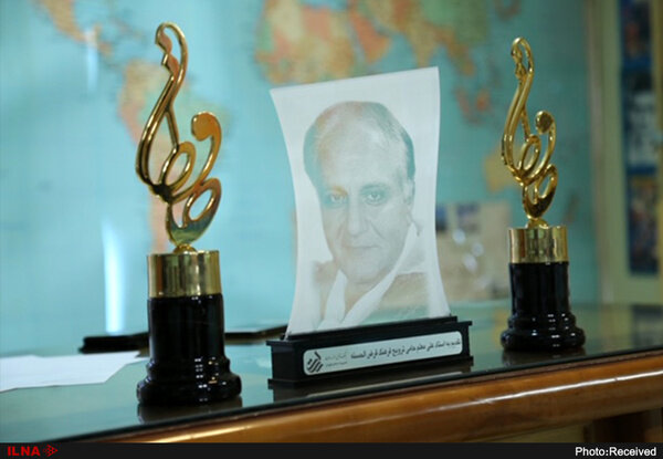 Picture of Ali Moallem, the founder of the Hafez Awards, who is seen between the Hafez trophies.