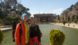 "Chinese travelers pose for a photo during their visit to Chehel Sotoun, a tourist destination in Isfahan, central Iran. The name, meaning ""Forty Columns"" in Persian, was inspired by the twenty slender wooden columns supporting the entrance pavilion, which, when reflected in the waters of the fountain, are said to appear to be forty."