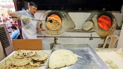 A baker bakes Iranian bread - known as taftoon - in Kuwait City in traditional clay ovens. Once ready he uses a long stick to reach in and pull out a steaming round loaf (Photo: AFP)