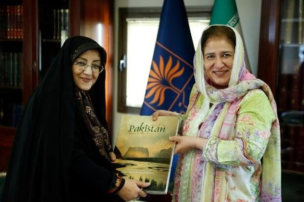 "NLAI director Ashraf Borujerdi (L) poses with Pakistani Ambassador Riffat Masood after receiving the book ""Pakistan"" from her during a meeting at the NLAI. (NLAI)"