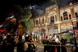 Portion of a fire truck, firefighters and passersby are seen in Hassanabad Sq., downtown Tehran, where a raging fire has just been distinguished, July 17, 2019. In the background smoke still rises from a Qajar-era building that encircles the square.
