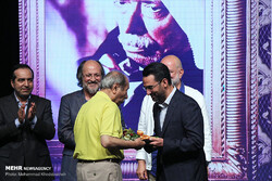 Actor Ali Nasirian (L) receives an award for his lifetime achievements from Information and Communication Technology Minister Mohammad Javad Azari Jahromi during the Cinema Tours Festival on Kish Isla