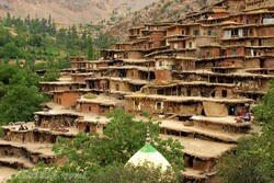 A view of the touristic village of Masuleh in Gilan province. It features earth-colored houses that are stacked photogenically on top of one another like giant Lego blocks, clinging to a mountainside so steep that the roof of one house forms the pathway for the next.