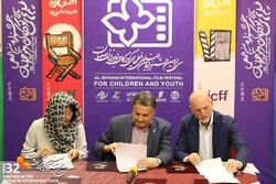 Seoul Guro festival representative Su-Dung (L), Isfahan festival director Alireza Tabesh (C) and Zero Plus festival director Nikolai Dann sign an MOU in the central Iranian city of Isfahan on August 2