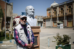 Actor Dariush Arjmand poses beside his bust after being unveiled in the Iran Television and Cinema Town on August 27, 2019. (Mehr/Mohammad Khodabakhshi)