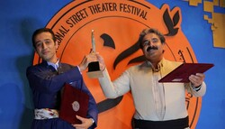 """Directors Asu Akram Ahmad (L) from Iraq and Mokhtar Mohammadi from Iran hold their award for best director for their co-production """"9 O'clock"""" during the closing ceremony of the 14th Marivan Internati"""