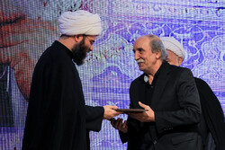 An unidentified winner receives his award from IIDO director Hojjatoleslam Mohammad Qomi during the Dibil Khuzai Awards – Ashura Book of the Year at the House of Humanities Thinkers in Tehran on Septe