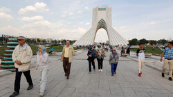 File photo: People walk pass the Azadi Tower, western Tehran. The inverted-Y-shaped monument is one of visual icons of the Iranian capital.
