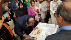 Korean artists Kwak Suk-son, surrounded by guests, does a painting at the opening ceremony of a joint exhibition by Korean and Iranian artists at the South Korean ambassador residence in Tehran on Nov