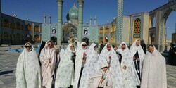 International female travelers pose for a photo while visiting a religious shrine in Aran-Bidgol, central Iran. They are clad in chadors, shapeless gowns that cover their entire bodies, to respect a dress code required for female pilgrims.