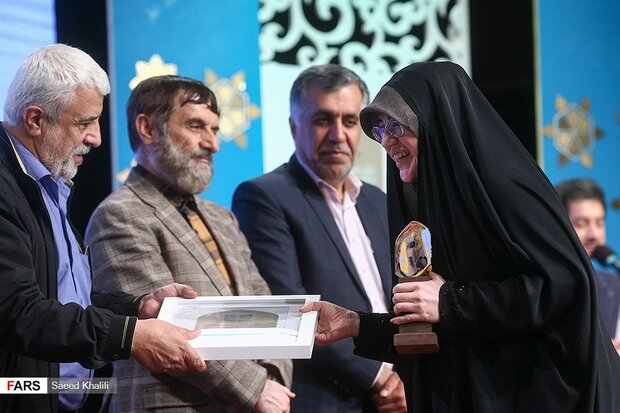 "Poet Fatemeh Nanizad (R) receives an award for ""Hi Commander"", her joint collection with Saeid Haddadian, during the first edition of the Martyr Hossein Hamedani Awards at Sureh Hall in Tehran on Nove"