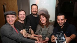 """Sorush Saeidi (R), actor and producer of the Iranian film """"Funfair"""", and other winners celebrate after receiving awards during the 32nd Foyle Film Festival at the Brunswick Moviebowl in Derry-Londonde"""
