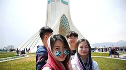 "File photo shows Chinese citizens in Tehran with Borj-e Azadi ""Azadi Tower"" in the background"