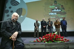 """Manuchehr Anvaar, the narrator of """"The Lovers' Wind"""", speaks during the opening ceremony of the 13th Cinema Verite at Tehran's Charsu Cineplex on December 9, 2019. (DEFC)"""