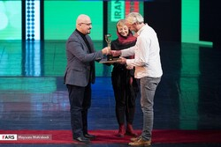 German director André Hörmann (R) receives his award from jury members Mehrdad Oskui (L) and Zlatina Rousseva during the closing ceremony of the 13th Cinéma Vérité at Tehran's Vahdat Hall on December