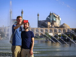 Foreign tourists use a mobile phone to take a selfie picture as they are standing at the UNESCO-registered Imam Square in Isfahan, central Iran. (Photo credit: IRNA)