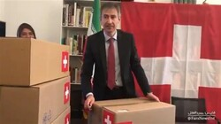Frame grab from a video published by Fars News Agency shows Swiss Ambassador to Tehran Markus Leitner's posing with medicine cartons inscribed with the Swiss flag after their transfer into the country.