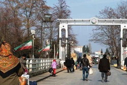 People walk toward an Iran-Azerbaijan border crossing gate
