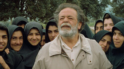 "Mohammad-Ali Keshavarz and schoolgirls from Koker act in a scene from ""Through the Olive Trees"", one of Abbas Kiarostami's movies from The Koker Trilogy."