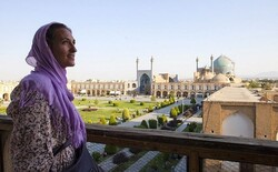 A foreign traveler poses for a photo while standing at the terrace of the 17th-century Ali-Qapu Palace, a top masterpiece of Iranian architecture, which punctuates the middle of two-story arcades encircling the enormous Imam Square; a UNESCO-registered site in Isfahan, central Iran.