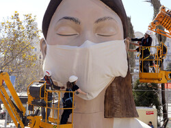 The World Health Organization called the COVID-19 viral disease a pandemic Wednesday. Here, workers in Spain place a medical mask on a figure that was to be part of the Fallas festival in Valencia. The festival has been canceled over the coronavirus outbreak. (Photo: Alberto Saiz/AP)
