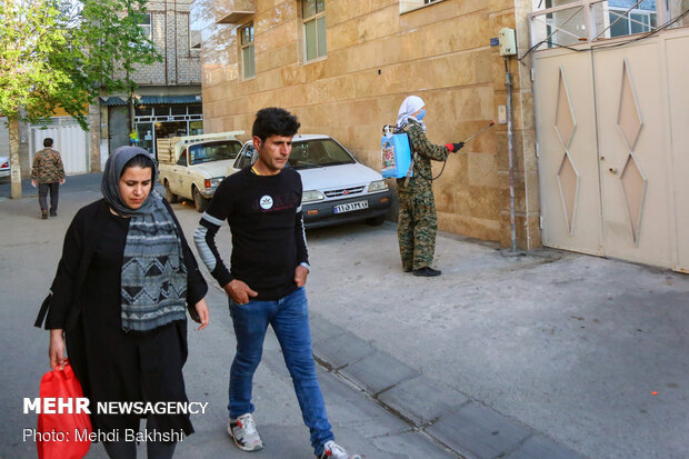 A seminary student from Russia disinfcteing thoroughfares in Qom
