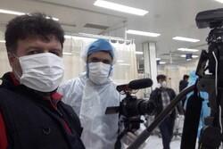 Javad Yaqmuri (L) and Mehdi Amini record short documentaries on coronavirus at the Kamkar Hospital in Qom.