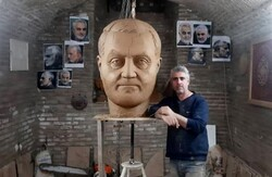 Sculptor Mohammad-Ali Jamali poses beside the head of Martyr Qassem Soleimani's statue at his atelier in Qazvin in an undated photo.