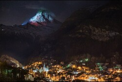 Mountain in Swiss lit up with a projection of Iran's flag