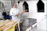 زنی که همپای شوهرش پای تنور نانوایی کار میکند