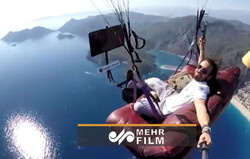 VIDEO: A paraglider flies off cliff while sitting on sofa